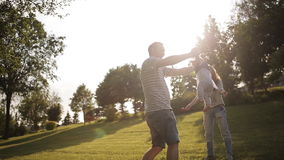 Young parents playing with little daughter in the park at sunset stock video footage