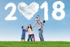 Young parents with children and numbers 2018. Young parents playing with their children in the meadow with clouds shaped numbers 2018 and heart royalty free stock photos