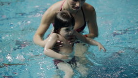 Young parents in the pool teaching his son to swim under water. The child learns to swim underwater in the pool stock video