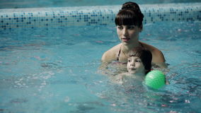 Young parents in the pool teaching his son to swim under water. The child learns to swim underwater in the pool stock video footage