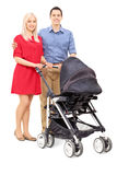 Young parents posing with a baby stroller Royalty Free Stock Images
