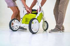 Young parents are preparing a green stroller for a child. Man and woman are posing on photo session on the background of royalty free stock photo