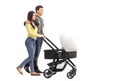 Young parents pushing a baby stroller Stock Photos