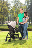 Young parents pushing a baby stroller in park Stock Photo