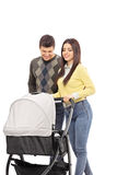 Young parents pushing a baby stroller Royalty Free Stock Photo