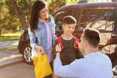 Young parents saying goodbye to their little child. Near school royalty free stock photo