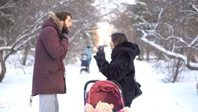 Young parents shouting at each other near a little baby in pink stroller while walking in winter park. Angry mother and stock image