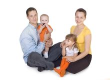 Young parents sit with children Stock Images