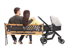 Young parents sitting on a bench with their baby Royalty Free Stock Image
