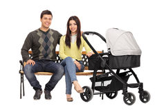 Young parents sitting on a wooden bench Royalty Free Stock Image