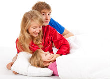 Young parents with sleeping daughter in bed Stock Photography