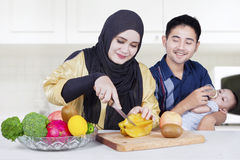 Young parents and son cooking with fruits Royalty Free Stock Photography