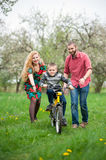 Young parents teaching his son to ride a bike. Happy parents teaching his son to ride a bike in spring garden. Family having fun against the background of Stock Photo