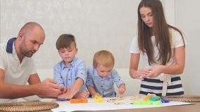 Young parents teaching their little boys how to make cookies. Professional shot in 4K resolution. 092. You can use it e.g. in your commercial video, business stock footage