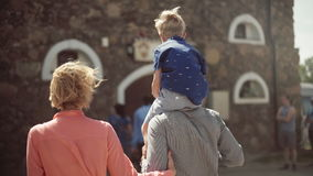 Young parents with their adorable son walking and having fun in courtyard stock video