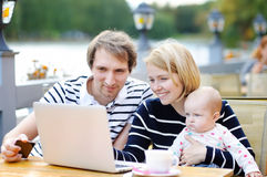 Young parents with their baby in outdoors cafe Stock Photo