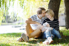 Young parents with their baby in sunny park Stock Photography