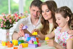 Parents and daughter playing with plastic blocks Stock Images