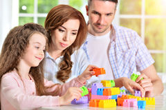 Parents and daughter playing with plastic blocks Royalty Free Stock Image