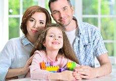 Parents and daughter playing with plastic blocks Stock Photos