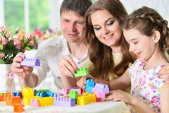 Parents and daughter playing with plastic blocks Royalty Free Stock Photography