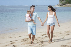 Young parents and their cute little daughter walking at the beac Royalty Free Stock Images