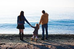 Young parents with their little daughter at beach Stock Images