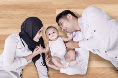 Young parents and their son lying on the floor Royalty Free Stock Images