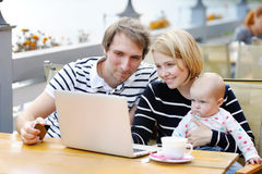 Young parents with their sweet baby in outdoors cafe Royalty Free Stock Photos
