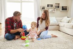 Young parents and toddler daughter playing in sitting room stock photo