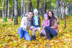Young parents and two kids in autumn park on a Royalty Free Stock Photos