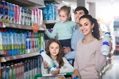 Young parents with two kids holding purchases in store Stock Photo