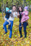 Young parents with two little daughters in autumn Stock Photos