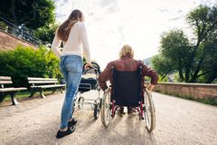 Young Parents In Wheelchair With Baby Stroller In The Park stock photography
