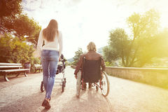 Young Parents In Wheelchair With Baby Stroller In The Park Stock Photos