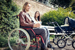 Young Parents In Wheelchair With Baby Stroller In The Park Stock Image