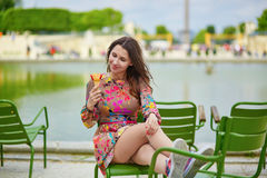 Young Parisian woman eating ice cream Stock Photo