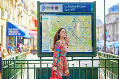 Young Parisian woman near the subway plan. Young beautiful Parisian woman near the subway plan, looking for the direction royalty free stock photos