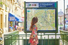 Young Parisian woman near the subway plan. Young beautiful Parisian woman near the subway plan, looking for the direction royalty free stock photography
