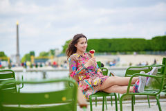 Young Parisian woman in the Tuileries garden, eating ice cream. Young Parisian woman in the Tuileries garden, sitting on a chair and eating ice cream Royalty Free Stock Photo