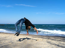 Young parkour man doing flip or somersault. Portrait of young parkour man doing flip or somersault on the beach Stock Photos