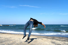 Young parkour man doing flip or somersault. Portrait of young parkour man doing flip or somersault on the beach. Freezed moment of flip Royalty Free Stock Photo