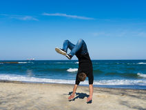 Young parkour man doing flip or somersault. Portrait of young parkour man doing flip or somersault on the beach. Freezed moment of flip Royalty Free Stock Photos