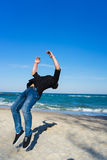 Young parkour man doing flip or somersault. Portrait of young parkour man doing flip or somersault on the beach. Freezed moment of beginning doing flip Royalty Free Stock Images