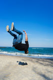 Young parkour man doing flip or somersault. Portrait of young parkour man doing flip or somersault on the beach. Freezed moment - finishing of flip Stock Photo