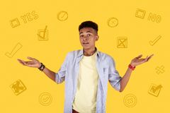 Young parson putting his hands up while making an important decision. Yes or no. Serious teenager putting his hands up while thinking about his future and making Stock Image