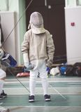 Young participant of the fencing tournament in white clothes and protective mask on the fencing tournament. Telephoto shot Stock Photos