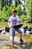 A young participant inspects the bottom of his pan Royalty Free Stock Photography