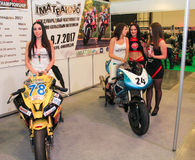 Young participants of the motor show. Models on motorcycles presented at the motor show Stock Photos