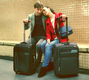 Young passengers with luggage waiting for train at subway statio Stock Photos